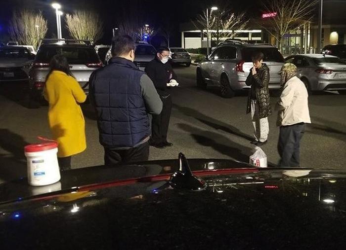 Gia đình ông Đinh cầu nguyện tại bãi đỗ xe Trung tâm Y tế Thuỵ Điển ở thành phố Issaquah tối 19/3 khi ông trong tình trạng nguy kịch. Ảnh: Seattle Times