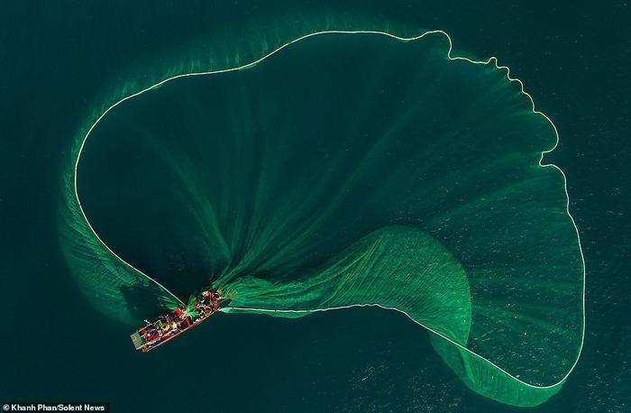 Thuyền đánh cánhiều sắc màu tung lưới khổng lồ xuống biển ở An Hải, tỉnh Phú Yên để bắt hàng ngàn con cá cơm.