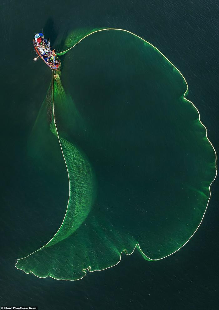 Lưới màu xanh lá cây to rộng khiến chiếc thuyền đánh cá trông nhỏ xíu nổi bật giữa làn nước xanh thẳm của biển cả.