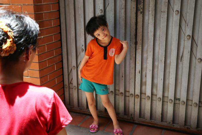 Bé gái bị down vội chạy ra ngoài tạo dáng. Cô bé có lẽ bị cuồng chân vì bị nhốt trong nhà quá lâu.