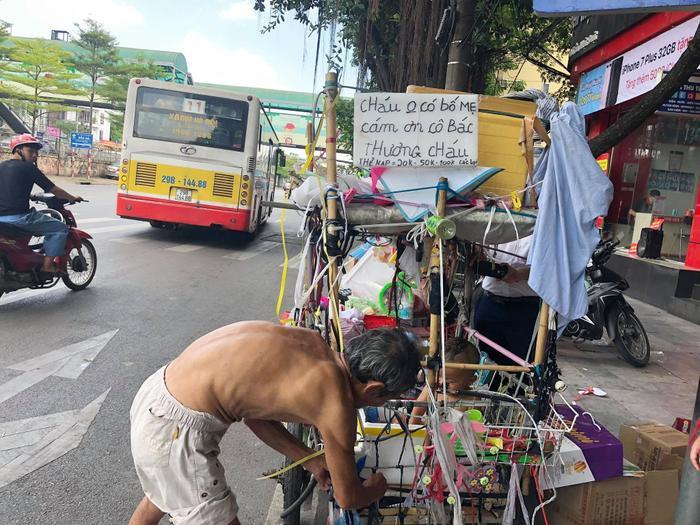 """Hình ảnh cháu bé cùng chiếc xe đẩy lang thang ở đường phố Hà Nội cùng tấm biển """"cháu không có bố mẹ, cảm ơn cô bác đã thương cháu""""."""