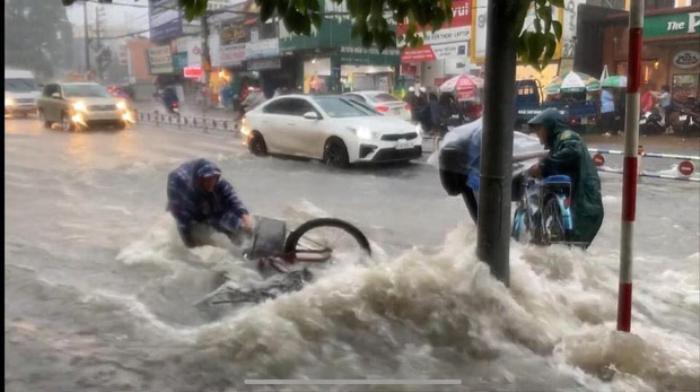 Bất chấp dòng nước chảy xiết trong cơn mưa lớn để đạp xe về nhà, nhóm học sinh ngã nhào xuống đường khiến nhiều người thót tim Ảnh 3
