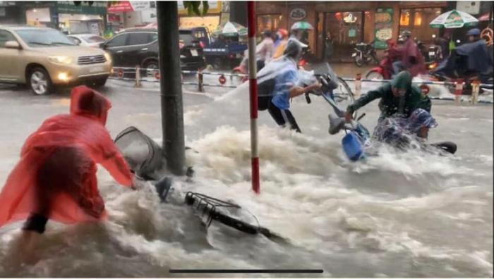 Bất chấp dòng nước chảy xiết trong cơn mưa lớn để đạp xe về nhà, nhóm học sinh ngã nhào xuống đường khiến nhiều người thót tim Ảnh 2