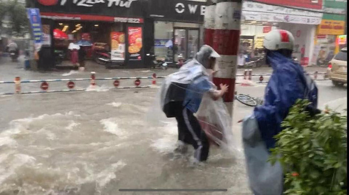 Bất chấp dòng nước chảy xiết trong cơn mưa lớn để đạp xe về nhà, nhóm học sinh ngã nhào xuống đường khiến nhiều người thót tim Ảnh 1