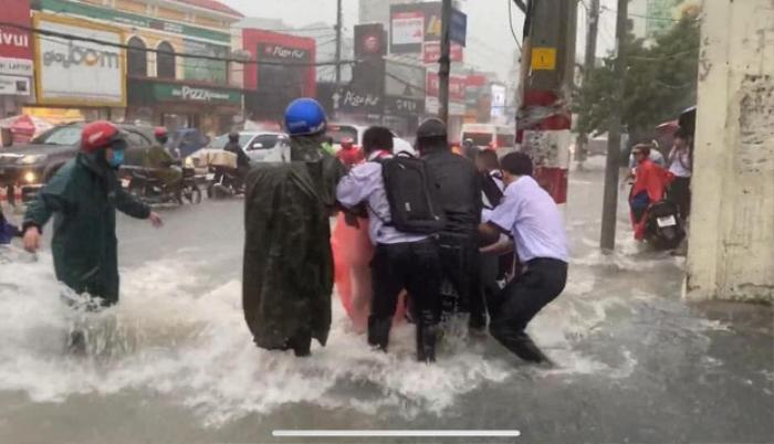 Bất chấp dòng nước chảy xiết trong cơn mưa lớn để đạp xe về nhà, nhóm học sinh ngã nhào xuống đường khiến nhiều người thót tim Ảnh 4