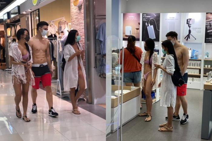 Hai cô gái mặc bikini dắt theo chàng trai cơ bắp đi mua sắm ở trung tâm thương mại Ảnh 1