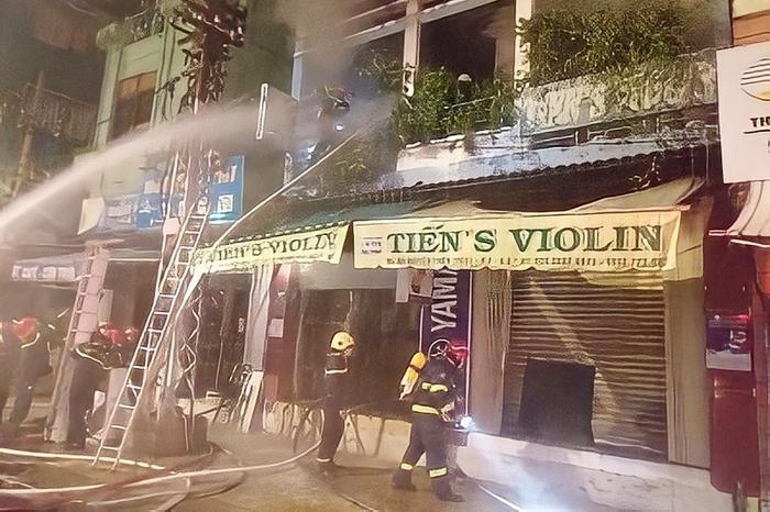 Cảnh sát cắt cửa cuốn, giải cứu 4 người trong căn nhà đang bốc cháy lúc rạng sáng Ảnh 1