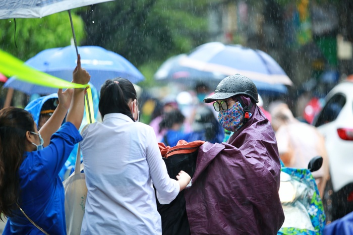 Hà Nội: Phụ huynh đội mưa đưa con đi thi, phải về lấy quần áo gửi đến phòng thi cho con thay Ảnh 10